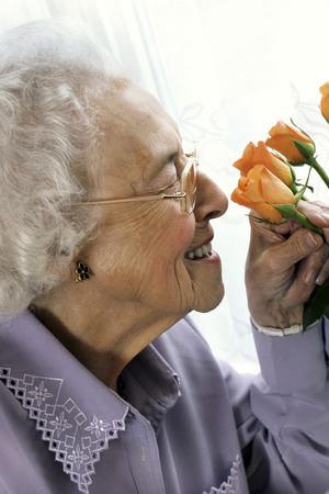 An old bespectacled woman sniffing flowers photo