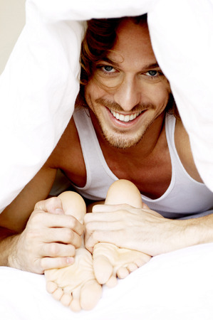 A guy hiding under the blanket holding his girlfriends feet photo