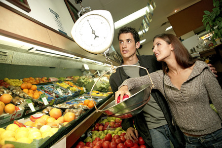 chose: A couple weighing the fruits that they chose Stock Photo