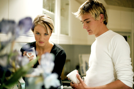 highlighted hair: A troubled looking couple standing in the kitchen