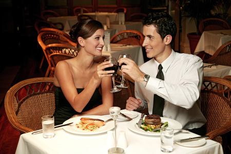 dinner wear: A couple having a toast in the restaurant Stock Photo