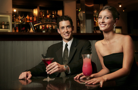 dinner wear: A couple in dinner wear sitting in a bar drinking cocktail