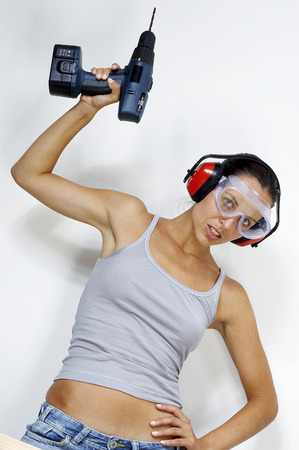driller: A woman with goggles and headphone raising a driller above her head Stock Photo