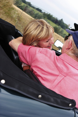 Back shot of an old man placing his hand around his wifes shoulder while sitting in the car photo
