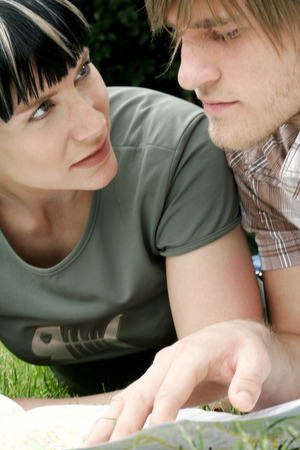 Close-up of a couple lying on the grass studying a map photo