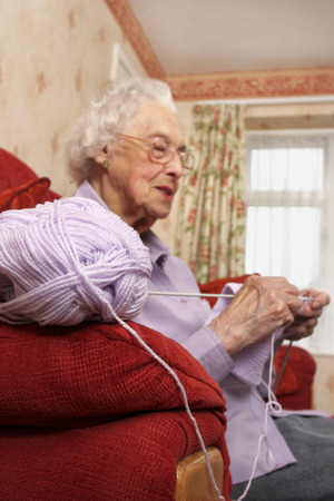 Side shot of an old bespectacled lady sitting on the couch knitting photo