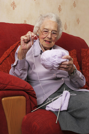 An old bespectacled lady sitting on the couch pulling her knitting thread photo