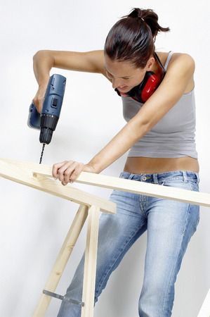 A woman drilling a hole on a wood Reklamní fotografie