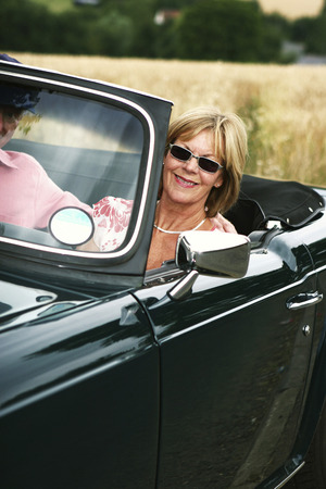 A woman sitting in the car while her husband driving photo