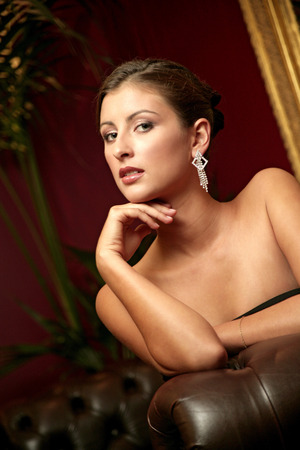 A stunning looking lady in a black dress sitting on the couch photo