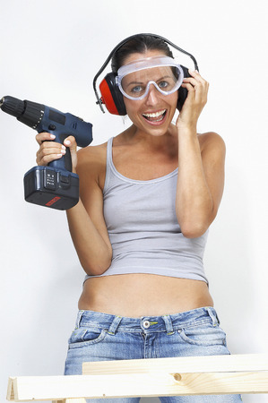 driller: A woman with goggles and headphone laughing while holding a driller Stock Photo