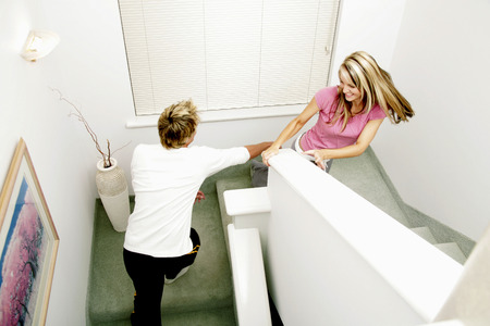 A lady running up the stairs while her boyfriend trying to catch her  photo