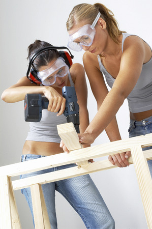 driller: A woman helping her friend to hold the wood as she is drilling