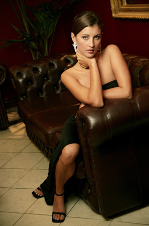 dinner wear: A stunning looking lady in a black dress sitting on the couch Stock Photo