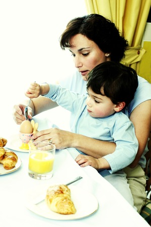 A young boy sitting on his mothers lap playing with food photo
