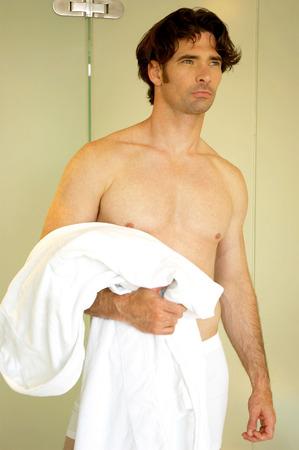 A shirtless man in boxer shorts holding a bathrobe photo