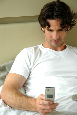 A man lying on his bed text messaging photo