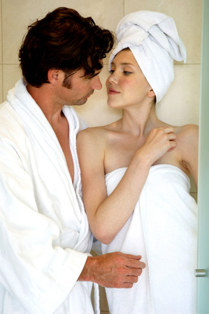 hair wrapped up: A woman smelling her husbands mouth in the bathroom Stock Photo
