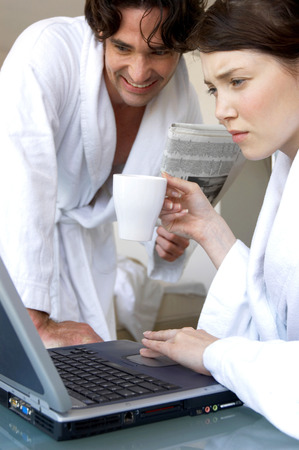 A woman in bathrobe using laptop while her husband watching Stock Photo - 26137607
