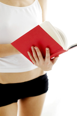 inner wear: Shoulder down shot of a woman in white camisole reading a book