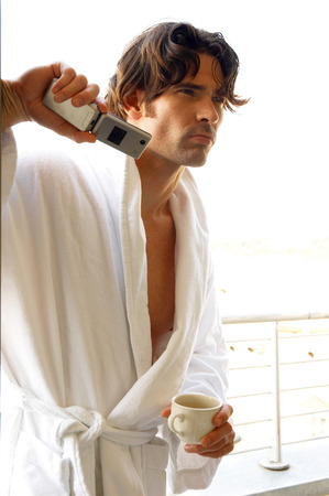 A man in white bathrobe holding a cup and a hand phone photo
