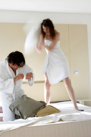 A couple pillow fighting on the bed photo