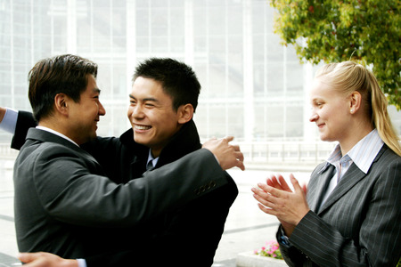 Two men hugging each other while a woman clapping her hands  photo
