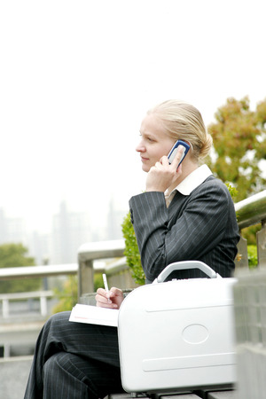desirous: A woman sitting on the bench talking on the hand phone