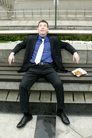 desirous: A man resting on a bench with his lunch by the side