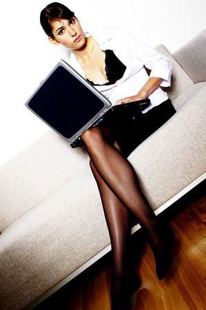 Sexy lady sitting on the couch using laptop
