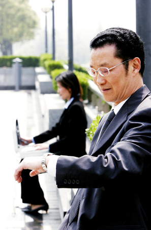 bespectacled man: A bespectacled man looking at his watch while a woman using her laptop
