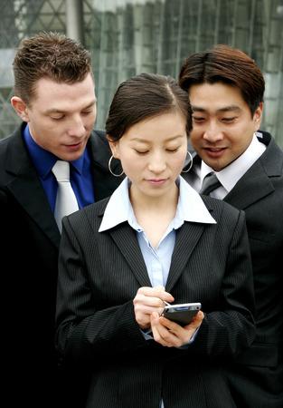 Two men watching a woman using a palmtop