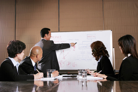 A man doing presentation while the others concentrating  photo