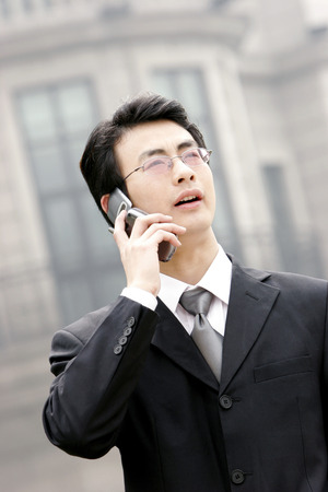 bespectacled man: A bespectacled man in business suit talking on the hand phone
