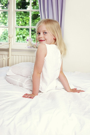 plushie: Back shot of a girl sitting on the bed while flashing a smile at the camera Stock Photo