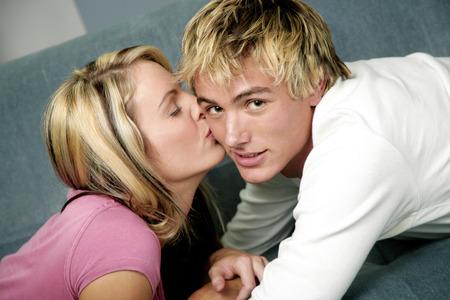 highlighted hair: Donna, dando il suo fidanzato un bacetto sulla guancia Archivio Fotografico