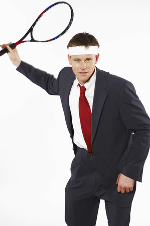 desirous: Man in business suit playing tennis  Stock Photo