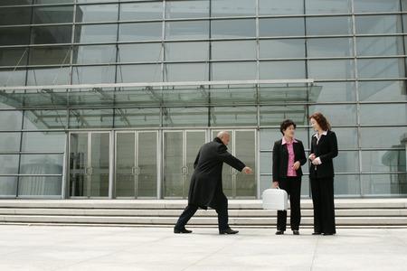 arracher: Homme chauve essayant d'arracher la serviette d'une femme d'affaires