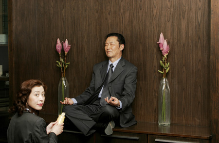 Woman worshipping a man who is sitting on the shelf meditating  photo