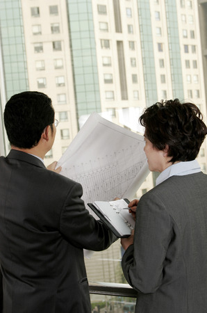 aspirant: Businessman discussing a building plan with his assistant