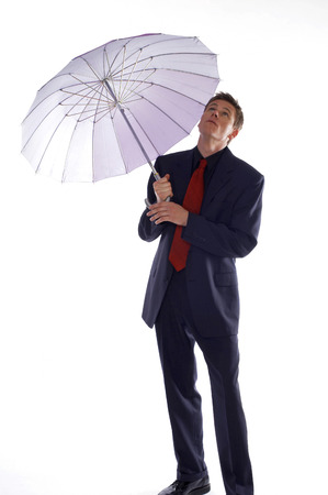 Man in business suit holding an umbrella while checking the weather  photo