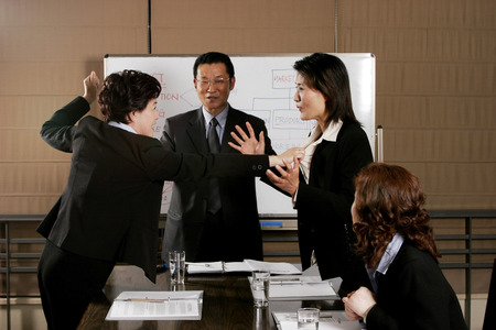 Manager trying to calm his employees from fighting  Stock Photo