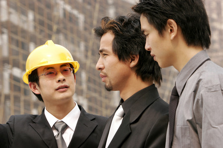 Architect discussing a building plan with his client at a construction site  photo