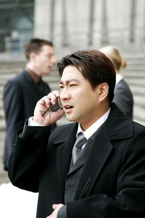 traje sastre: Un hombre en traje de negocios hablando por el tel�fono de la mano Foto de archivo
