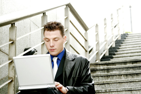 desirous: A man sitting on the stairs using his laptop