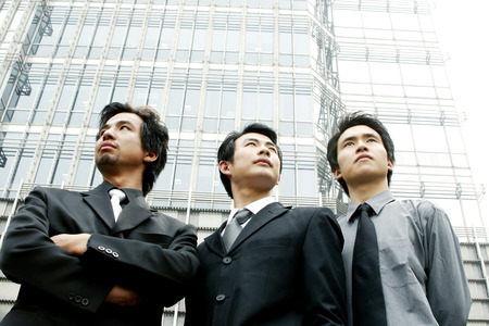 desirous: Three businessmen standing in front of the building