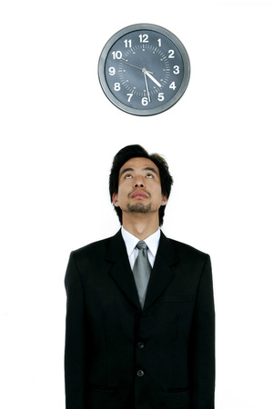 corporate waste: Man in business suit looking at the clock  Stock Photo