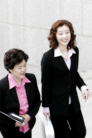 Two career women talking while walking up the stairs  photo