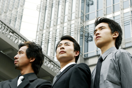 Three businessmen standing in front of the building  photo