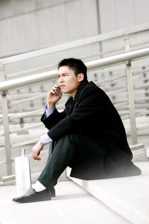 desirous: A man sitting on the stairs talking on the hand phone